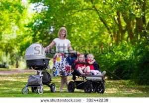 young-mother-walking-in-a-park-with-children-in-pushchair-mom-and-kids-in-a-buggy-walk-in-forest-302442239
